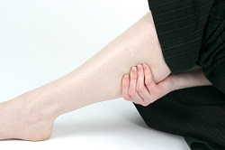 woman holding sore leg muscle