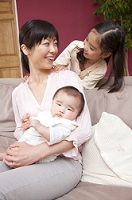 赤ちゃんを抱っこする母親の肩に手を置く娘